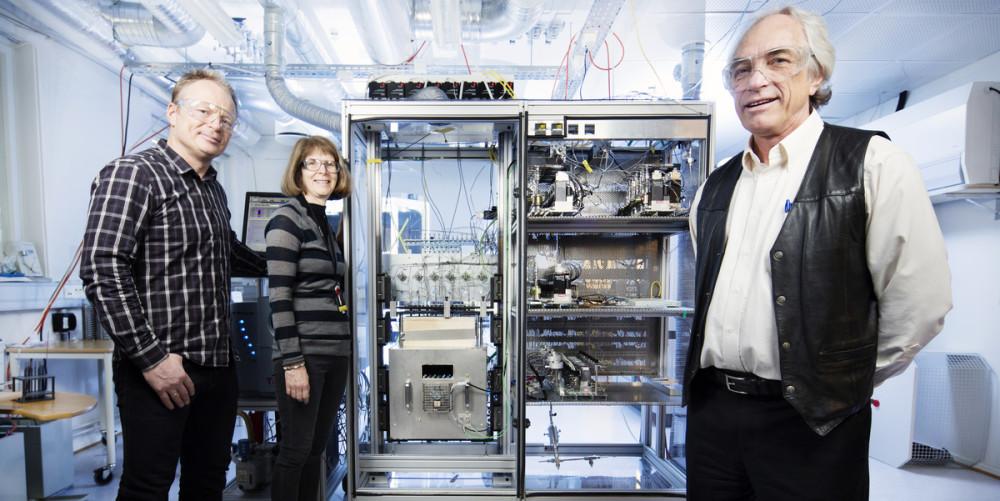 To menn og en kvinne flankereret kammer som utgjør et mini-laboratorium