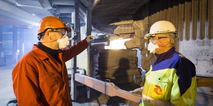 Silisiumindustrien i Norge er i gang med å redusere støvkonsentrasjonen i lufta rundt operatørene. Til fjerning av støv fra tappingen har Bernd Wittgens fra SINTEF (til v.) og Halvard Tveit fra Elkem og NTNU vært med på å utvikle et nytt avsug som Elkems verk på Thamshavn var først ute med å ta i bruk. Foto: SINTEF / Thor Nielsen