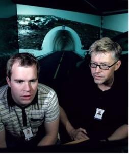 To menn menn sitter foran datautsyr i forkant av store videoskjermer som viser åpningen til veitunnel.