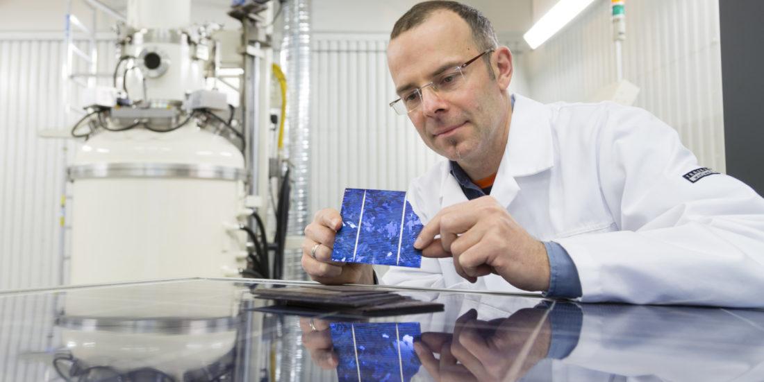 Mann i hvit frakk sitter på laboratorium der han ser på solcelle han holder i hendene.