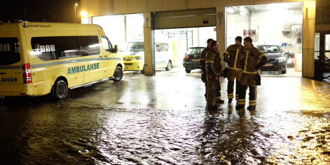 Ambulanse og brannfolk ses inne i oversvømmet underetasje ved sykehus.