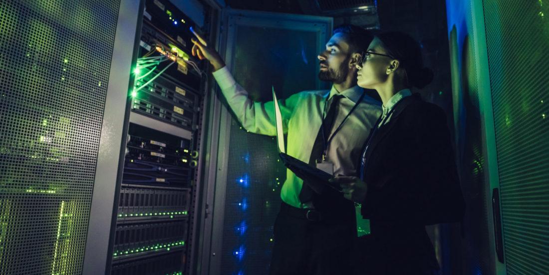 Mann og kvinne ser mot vegg av dataskjermer inne på et datasenter.