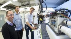 Tre menn står foran laboratoriebenk med teknisk utstyr, rør og ledninger
