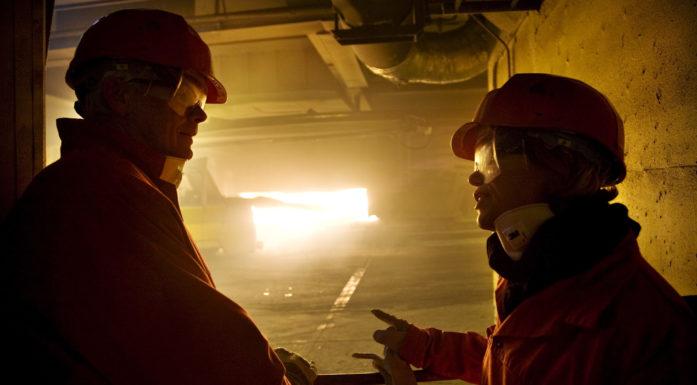 Silhuett av to mennesker med hjelm og kjeldress foran smelteovn der flammer ses gjennom åpen luke.