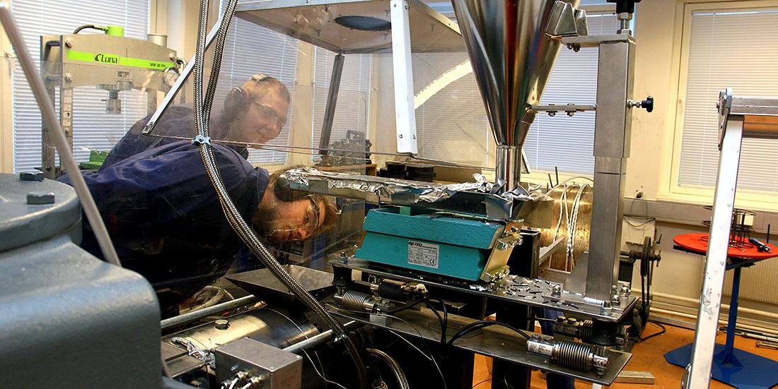 Denne maskinen maler opp aluminium til aluminiumsspon, som kan bli til aluminiumsarmering i betongkonstruksjoner. Det kan gi store klimafordeler. Geir Langelandsvik og OlavRagnvaldsen overvåker skrue-ekstruderen. Foto: Wenche Margrethe Kulmo/NTNU