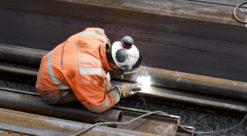 Bygningsarbeider i oransje kjeldress og hvit hjelm ses bakfra i det vedkommende gjør sveisearbeid på stålbjelke