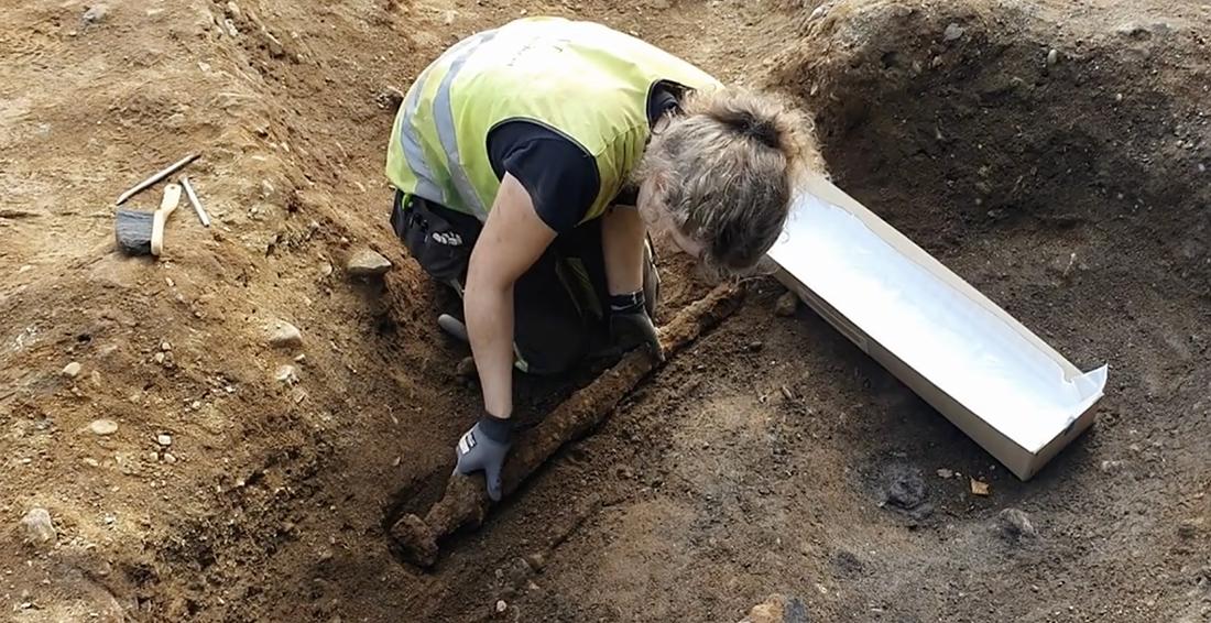 Bildet viser Astrid Kviseth ta opp et vikingsverd fra jorda