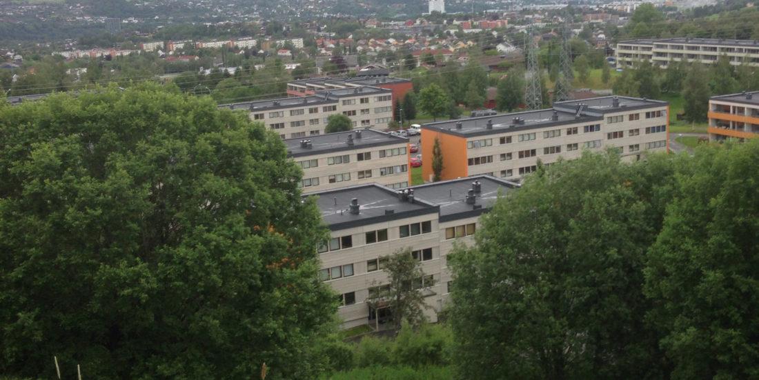 Eldre blokkbebyggelse i grønne omgivelser.
