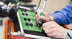 Nærbilde av hånd med loddebolt, lodding på grønn plate med elektroniske kretser.